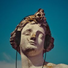 Classical statue wearing headphones
