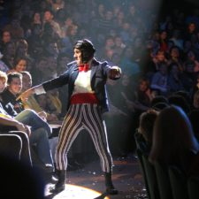 Man in a clown costume dancing around an audience