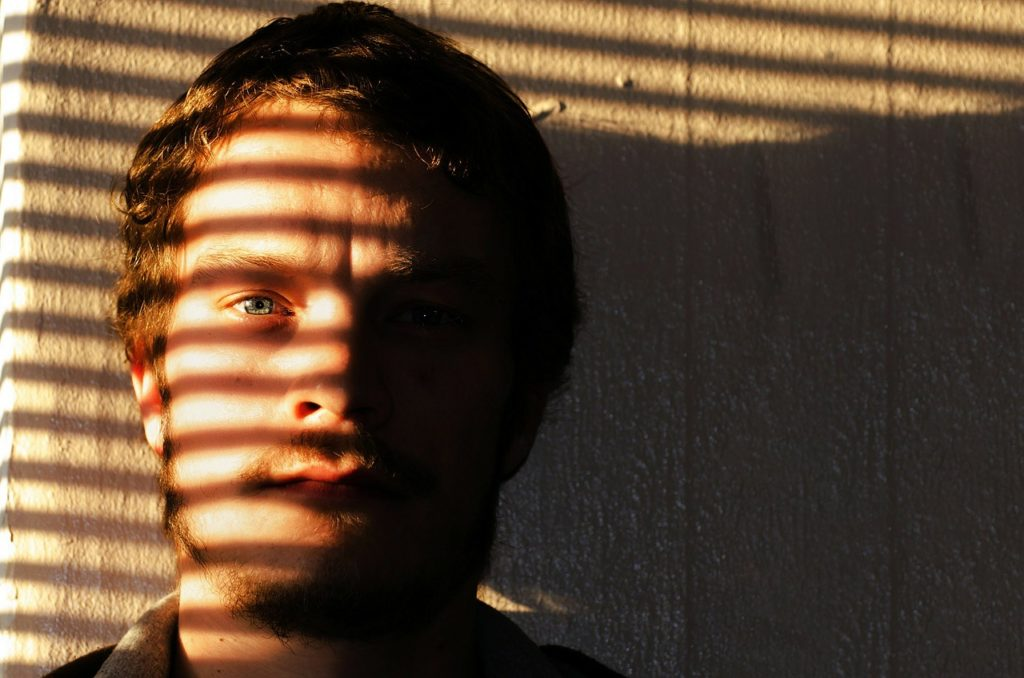 Man crying, shutter shadows across his face