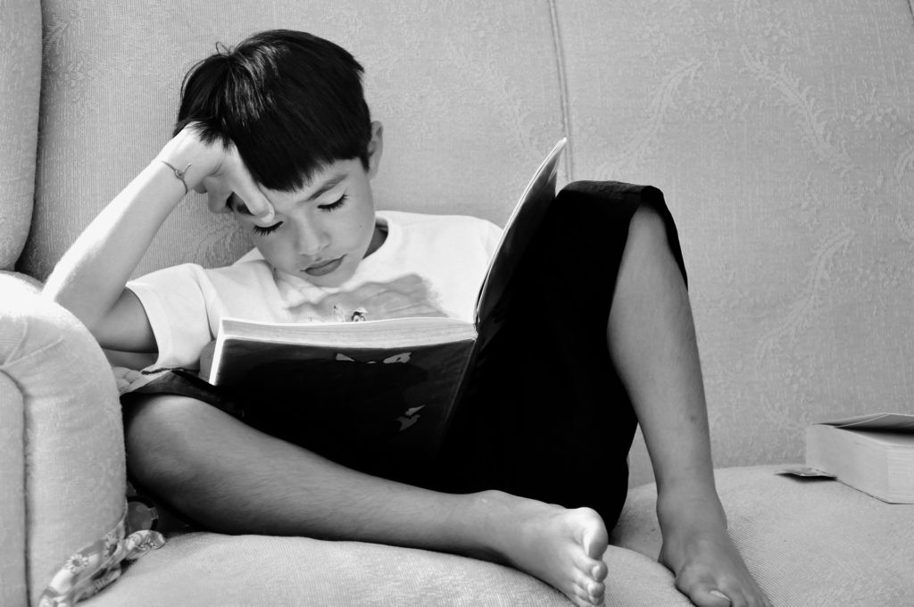 Boy sitting on a sofa, reading