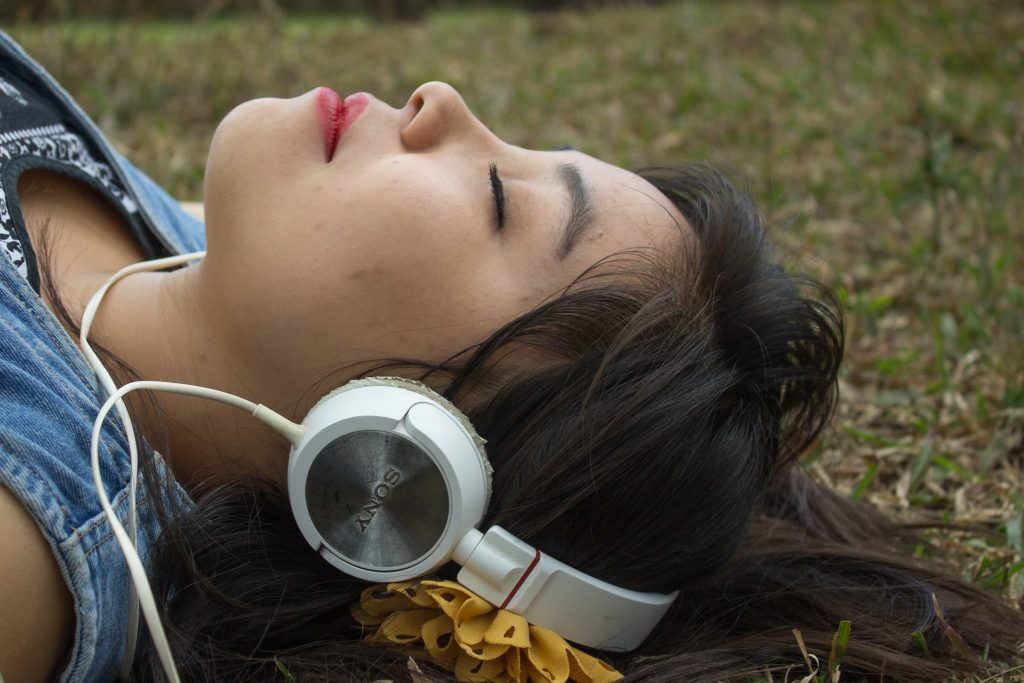 Woman lying in park with her eyes closed listening on headphones