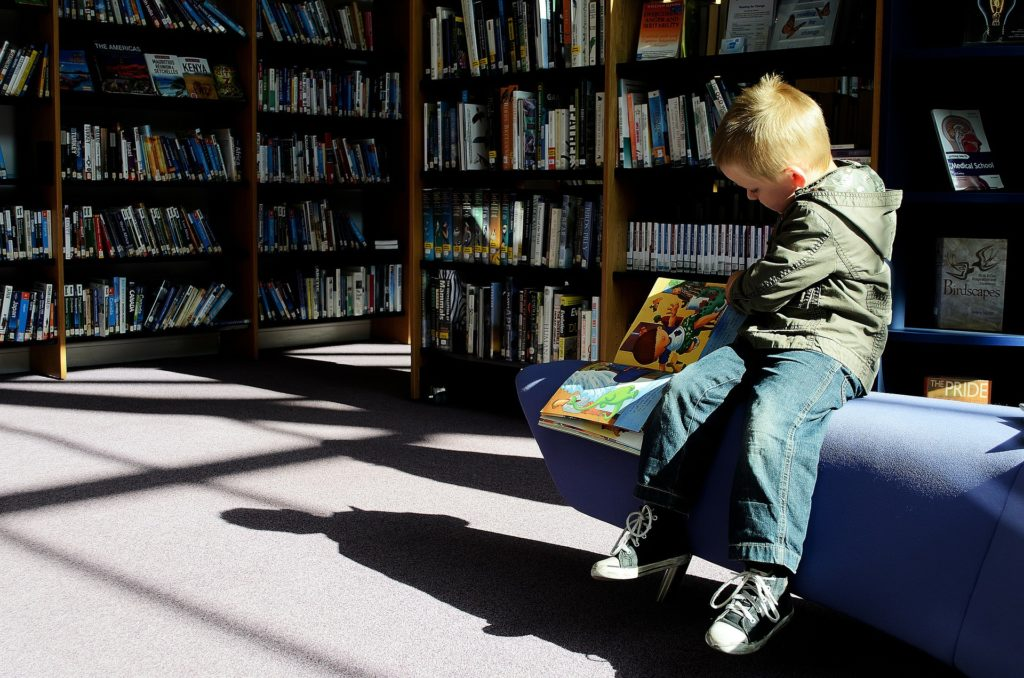 Child sitting reading a picture book in a library