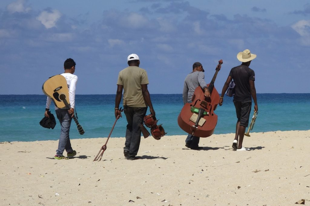 Four musicians walking away on a beach