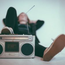 Person lying back with their foot on an old radio player, listening