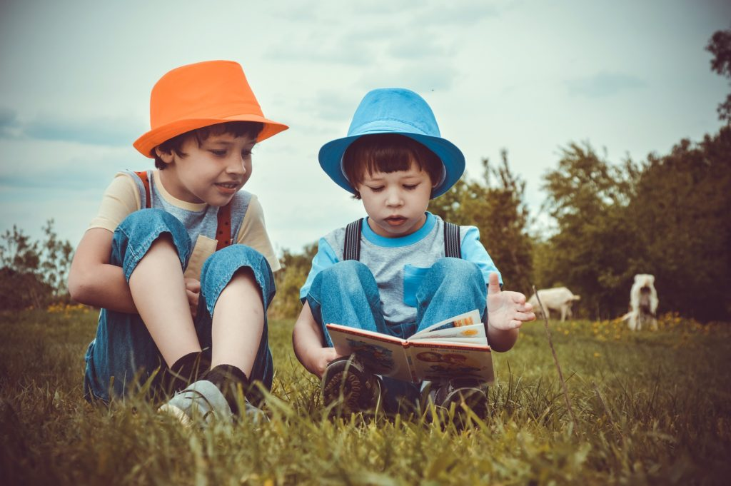Two young boys reading and discussing a book