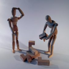 Two wooden men stacking a puzzle