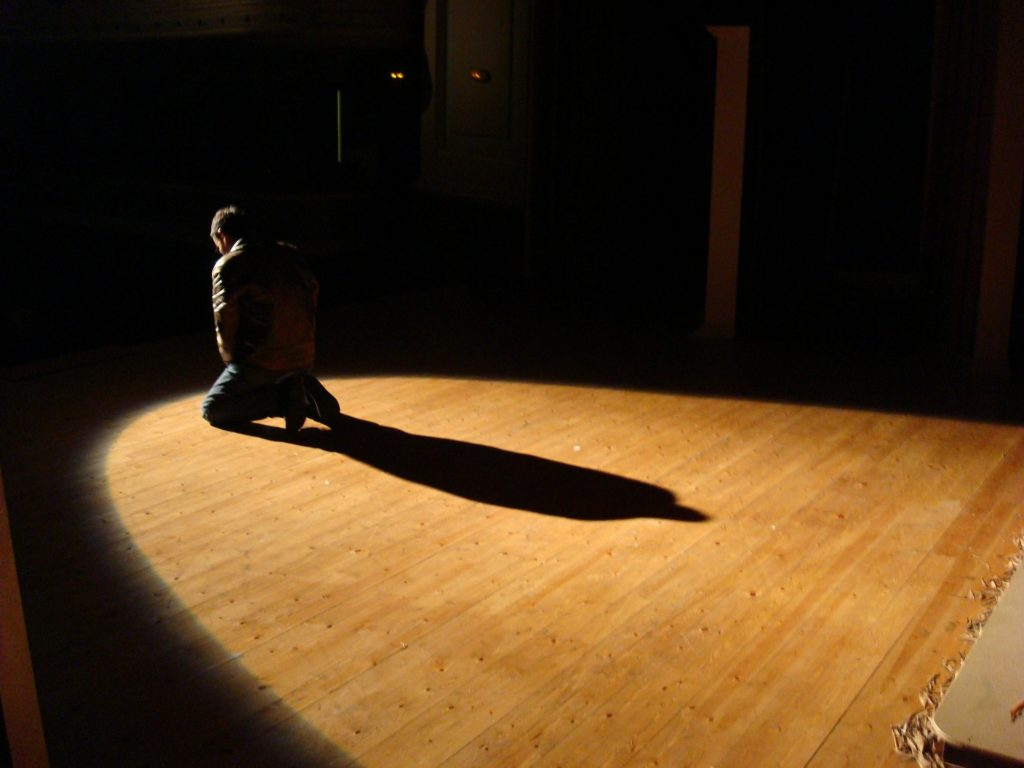 Man on his knees in the spotlight of a stage