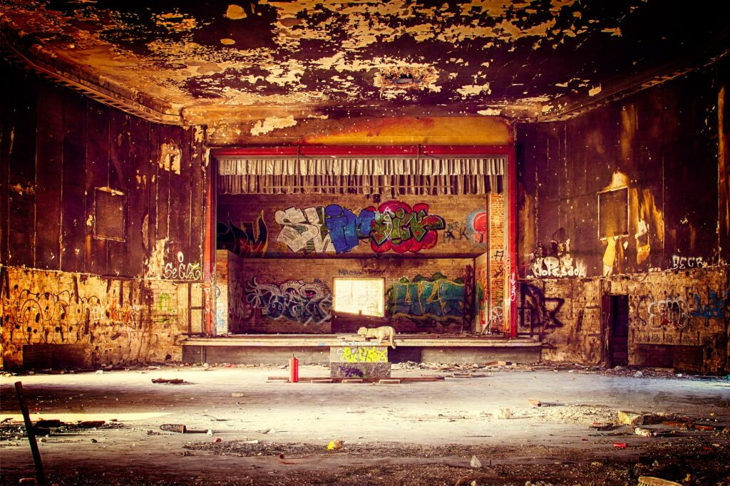 Abandoned theatre with peeling walls and graffiti