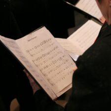 Singer holding a folder of choral music